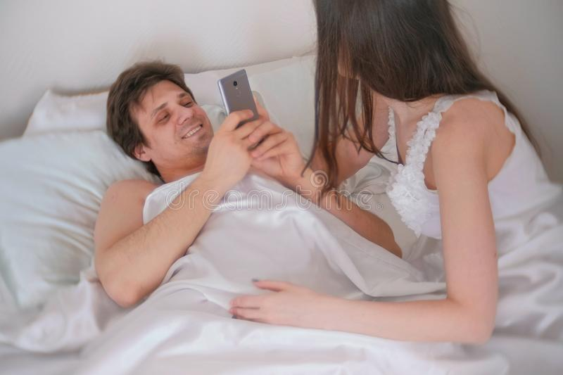 Mężczyzna fotografuje kobiety na telefonie komórkowym Pary kobiety i mężczyzna lying on the beach w łóżku Intymny związek, płeć zdjęcia stock