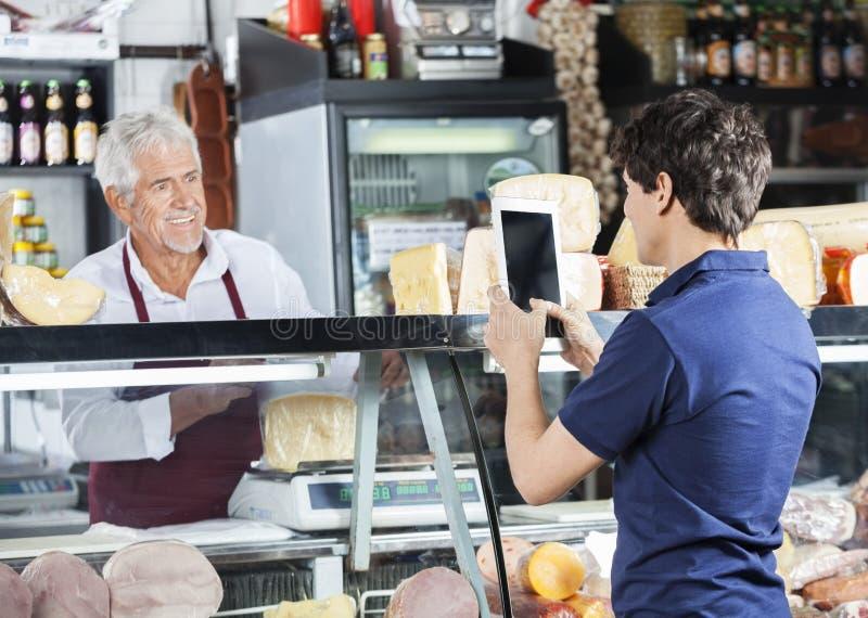 Mężczyzna Fotografuje sprzedawcy kocowania ser W sklepie obrazy royalty free