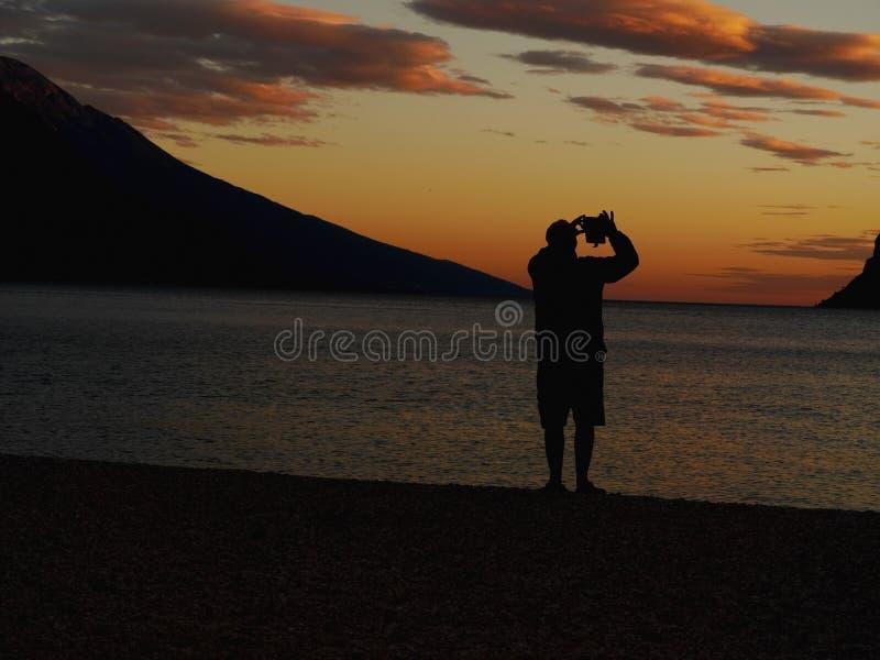 Mężczyzna fotografuje zmierzch z telefonem zdjęcie royalty free