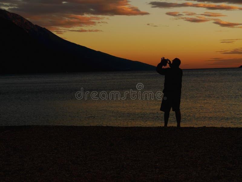 Mężczyzna fotografuje zmierzch z telefonem zdjęcia royalty free