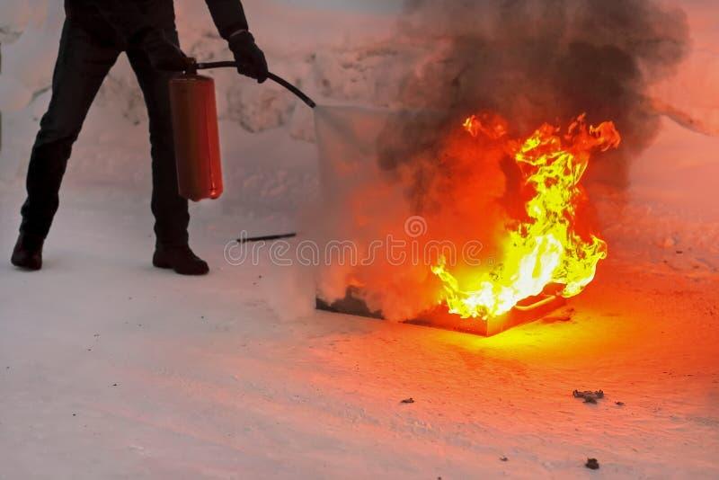 Mężczyzna gasi otwierającego ogień z pożarniczym gasidłem Kształcić urzędników i społeczeństwa używać ogienia fotografia royalty free
