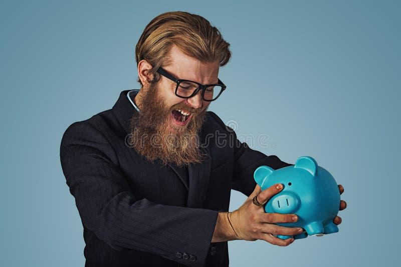 Mężczyzna gniewny przy jego prosiątko bankiem próbuje łamał je w górę zdjęcia stock