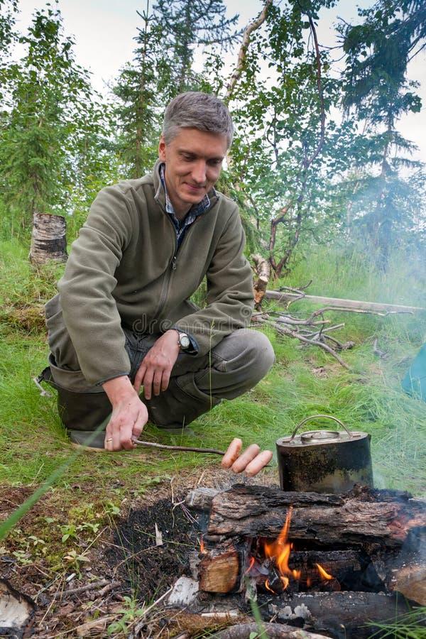 Mężczyzna gotuje kiełbasy na ogieniu fotografia royalty free