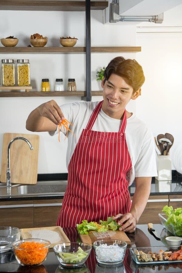 Mężczyzna gotuje wyśmienicie i zdrowego jedzenie w loft kuchni na słonecznym dniu w czerwonym fartuchu przygotowa? warzywa sa?atk obraz stock