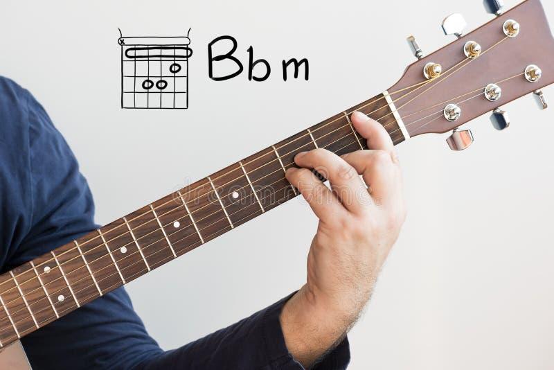 Mężczyzna grający w akordy gitarowe na tablicy, Chord B flat minor fotografia stock