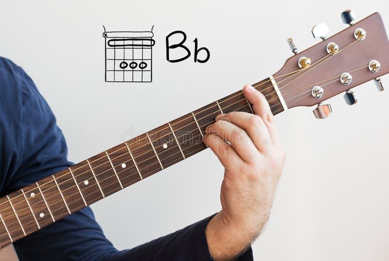 Mężczyzna grający w akordy gitarowe na tablicy, Chord B płaski zdjęcia stock