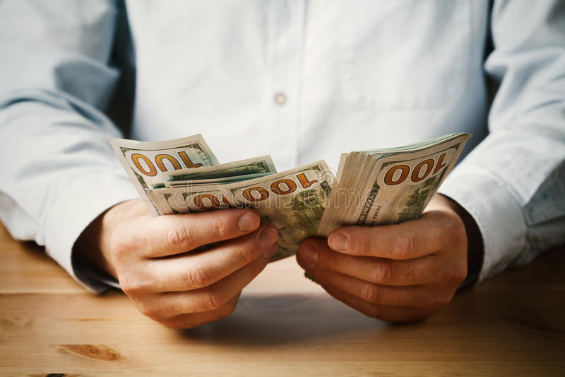 Mężczyzna hrabiowski pieniądze spienięża wewnątrz jego rękę Gospodarka, oszczędzanie, pensja i daruje pojęcie zdjęcia royalty free