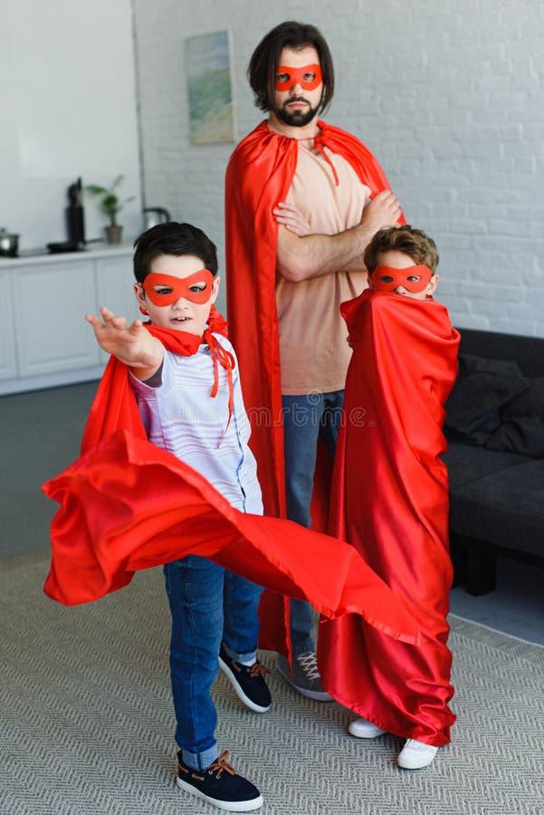 mężczyzna i śliczni mali synowie w czerwonych bohaterów kostiumach fotografia royalty free