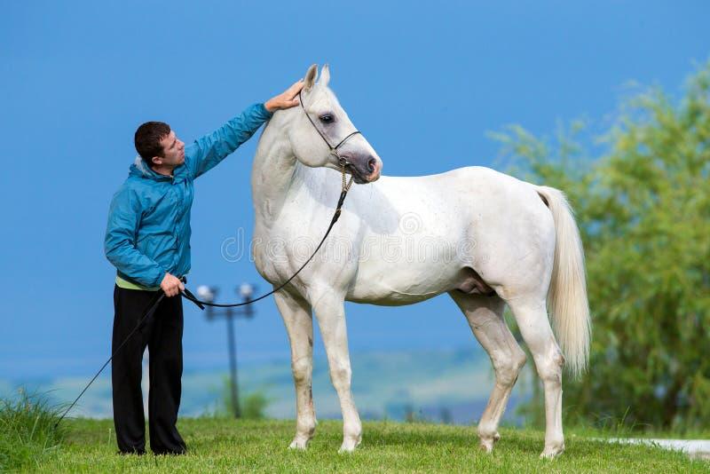 Mężczyzna i biały koń zdjęcia stock