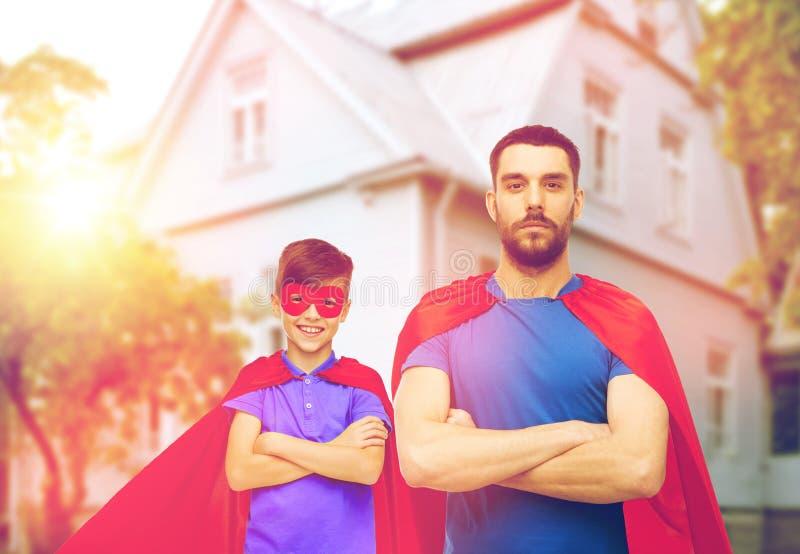 Mężczyzna i chłopiec jest ubranym bohatera przylądek maskowego i czerwonego fotografia royalty free