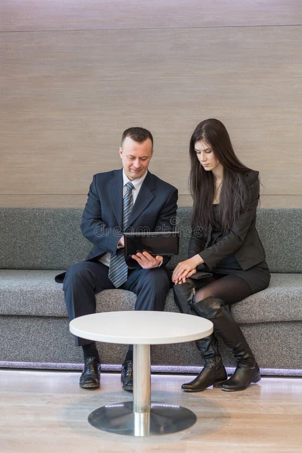 Mężczyzna i dziewczyna w garniturach siedzi na kanapie obraz stock
