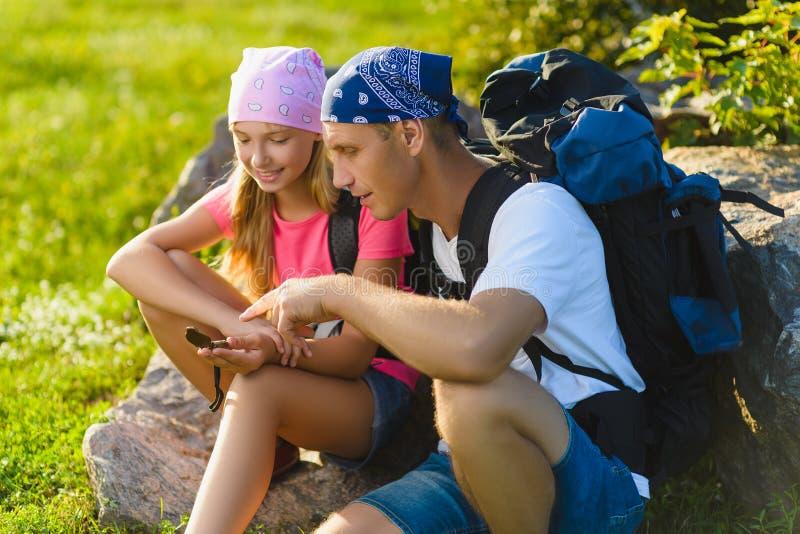 Mężczyzna i dziewczyna z plecakiem odpoczynkowym i patrzeje kompas obrazy stock