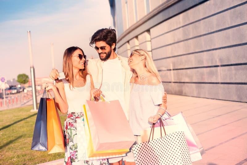 Mężczyzna i dziewczyny z szczęśliwymi twarzami z udziałem torba na zakupy zdjęcia royalty free