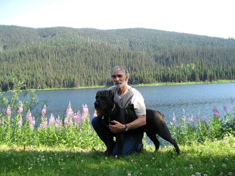 Mężczyzna i jego pies rzeką zdjęcie royalty free