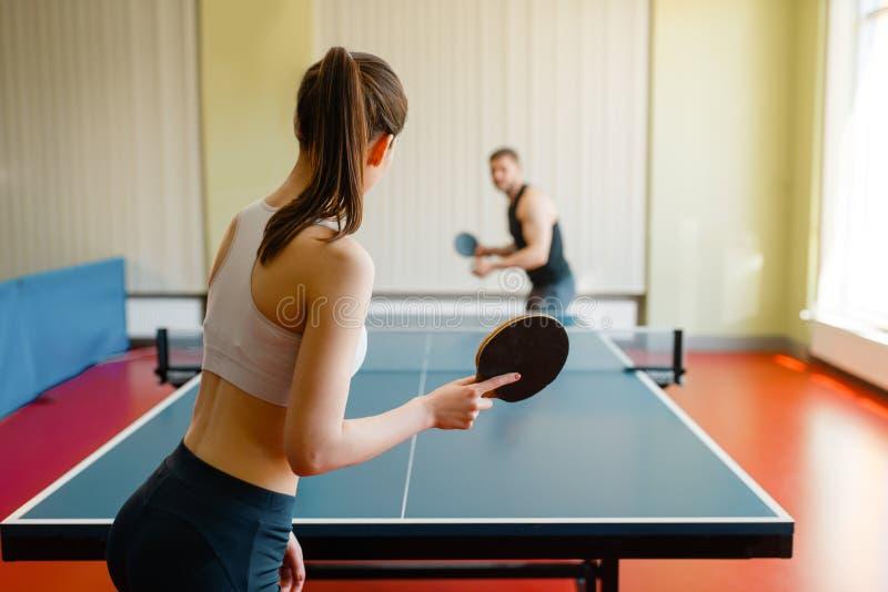 Mężczyzna i kobieta bawić się śwista pong indoors obraz stock