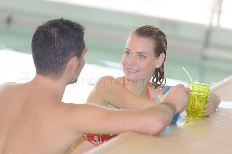 Mężczyzna i kobieta ma napój na pływackim basenie zdjęcia royalty free