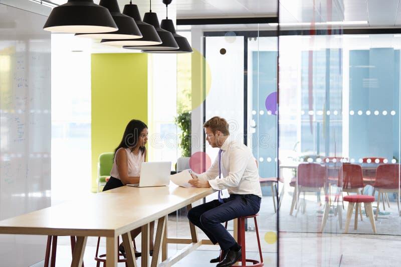 Mężczyzna i kobieta ma nieformalnego spotkania przy pracą fotografia stock