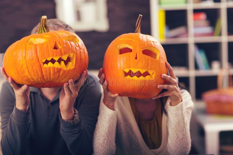 Mężczyzna i kobieta ma zabawę z pomarańczową Halloweenową banią obraz royalty free