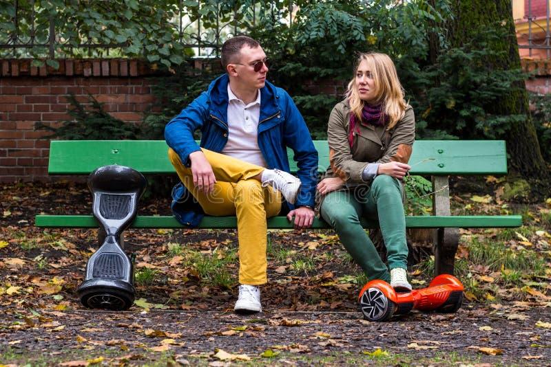 Mężczyzna i kobieta na ławce z hoverboards obraz royalty free