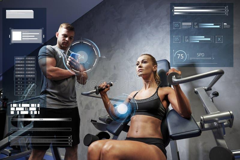 Mężczyzna i kobieta napina mięśnie na gym maszynie fotografia stock