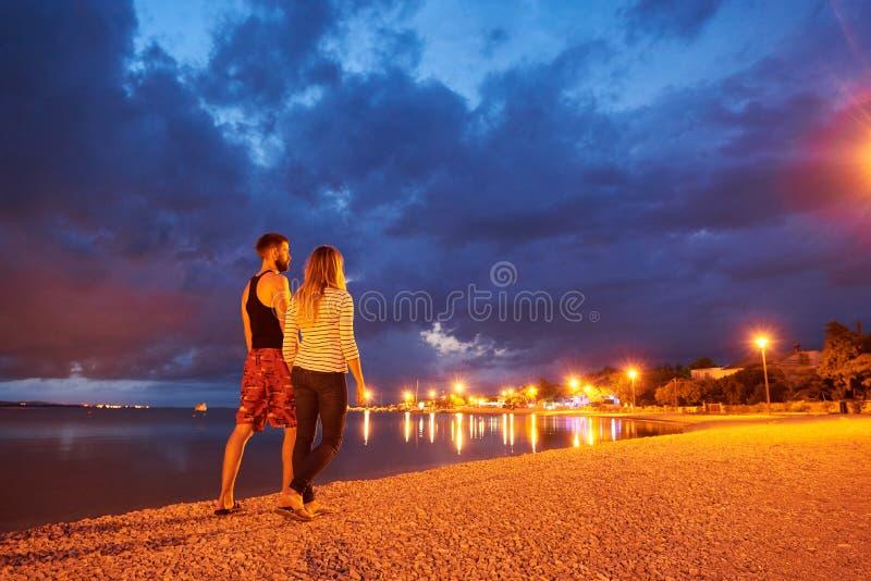 Mężczyzna i kobieta odpoczywa na otoczak plaży przy półmrokiem na spokój wody chmurnego nieba dramatycznym błękitnym tle obraz stock