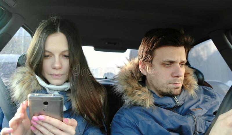 Mężczyzna i kobieta patrzeje coś w ich telefonach komórkowych siedzi w samochodzie Frontowy widok zdjęcia stock
