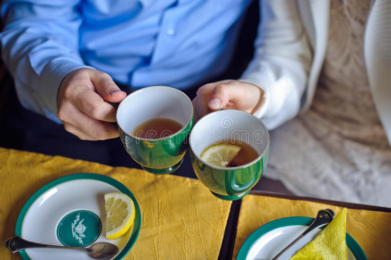 Mężczyzna i kobieta pije czarnej herbaty z cytryną filiżanki zdjęcie royalty free