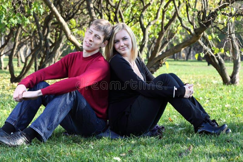 Mężczyzna i kobieta siedzimy na trawie i sen w parku z powrotem popierać