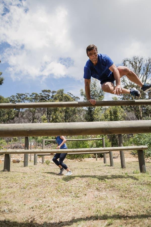 Mężczyzna i kobieta skacze nad przeszkodami podczas przeszkoda kursu fotografia stock