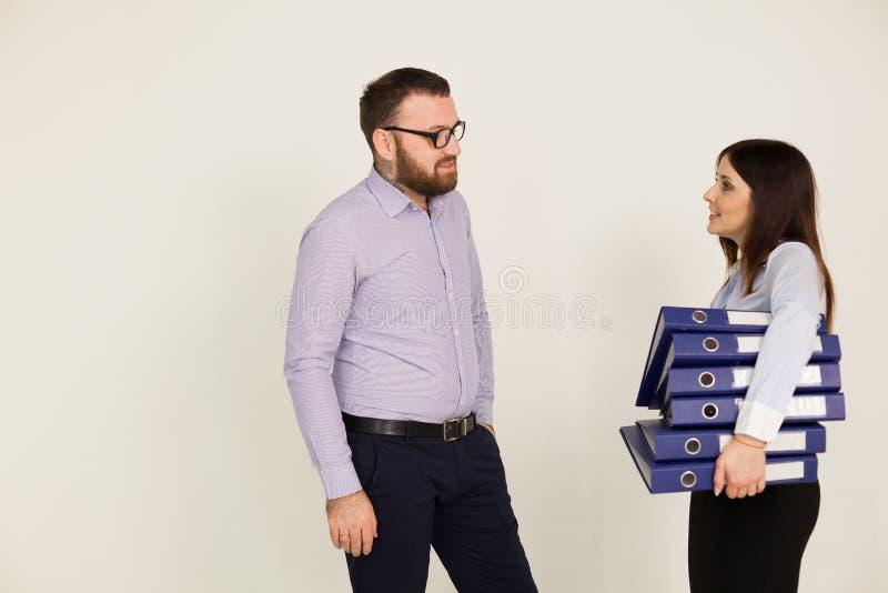 Mężczyzna i kobieta spotykaliśmy przy biurem wiele pracujących papiery zdjęcia royalty free