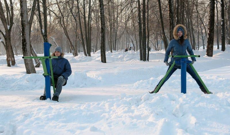 Mężczyzna i kobieta w niebieskich marynarkach angażujemy w symulantach w zima parku Frontowy widok obraz stock