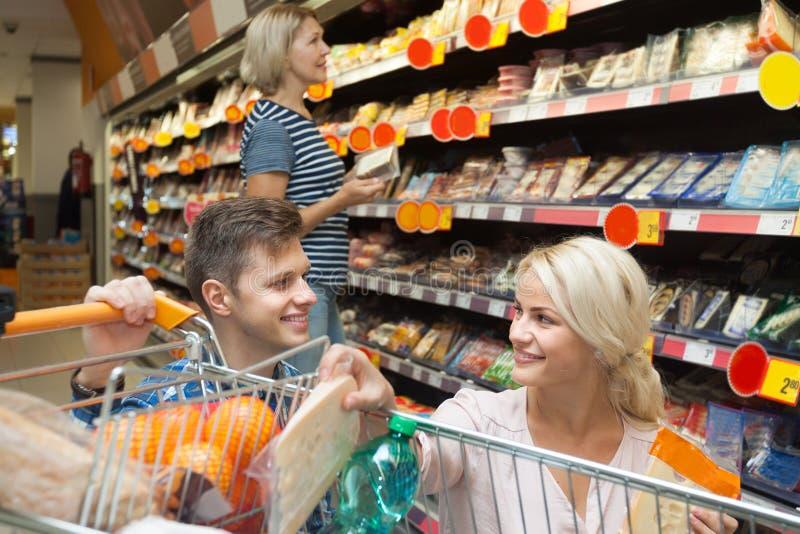 Mężczyzna i kobieta wybieramy ser w wydziałowym sklepie obraz stock