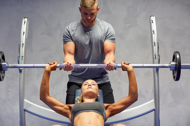Mężczyzna i kobieta z barbell napina mięśnie w gym fotografia stock