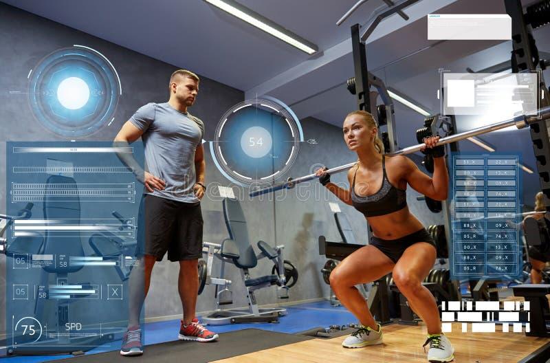 Mężczyzna i kobieta z barem napina mięśnie w gym zdjęcie royalty free