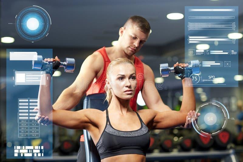 Mężczyzna i kobieta z dumbbells w gym fotografia royalty free