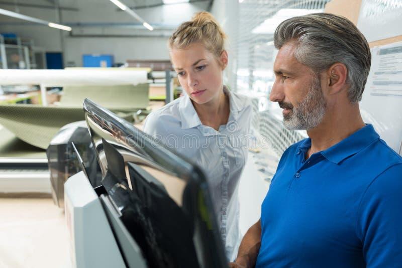 Mężczyzna i kobieta z laptopem w warsztacie fotografia stock