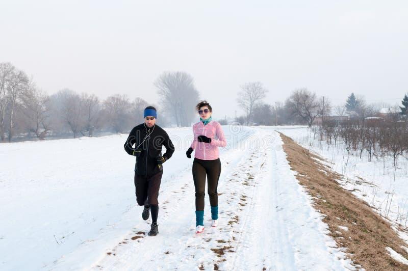 Mężczyzna i kobiety bieg na śniegu zdjęcie royalty free