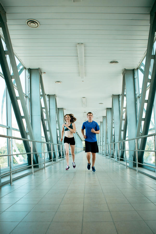 Mężczyzna i kobiety bieg w nowożytnej bridżowej budowie fotografia stock