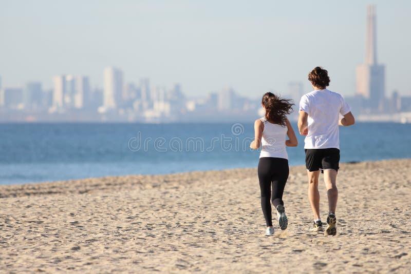 Mężczyzna i kobiety bieg w plaży obrazy royalty free