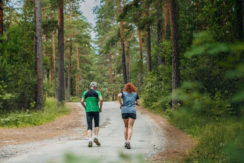 Mężczyzna i kobiety bieg wzdłuż drogi w lesie obraz royalty free