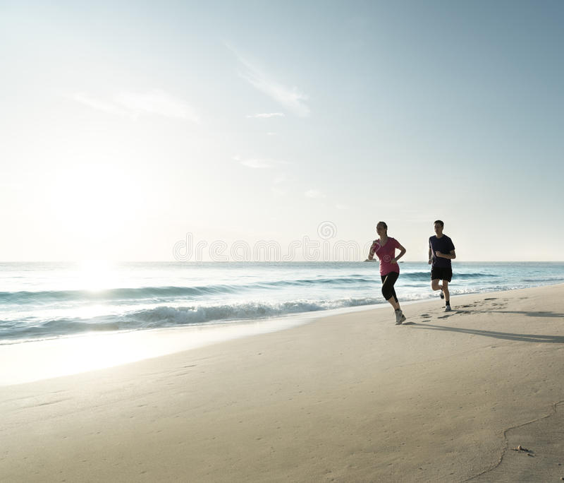 Mężczyzna i kobiety biega na tropikalnej plaży przy zmierzchem zdjęcie royalty free