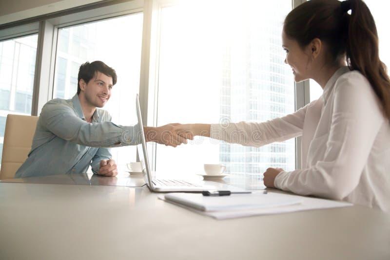 Mężczyzna i kobiety handshaking przy biurem, biznesowy spotkanie, akcydensowy inte zdjęcie royalty free