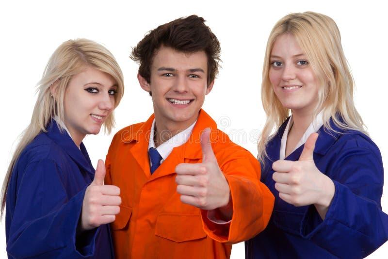 Mężczyzna I kobiety Jest ubranym Ochronną pracy odzież Pokazuje kciuk Up obrazy stock