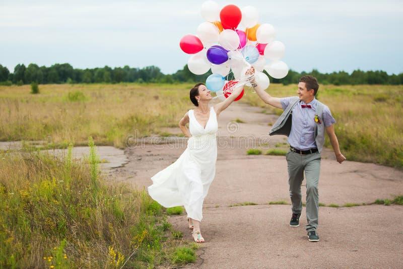 Mężczyzna i kobiety mienie wewnątrz wręcza dużo kolorowych lateksowych balony obrazy royalty free