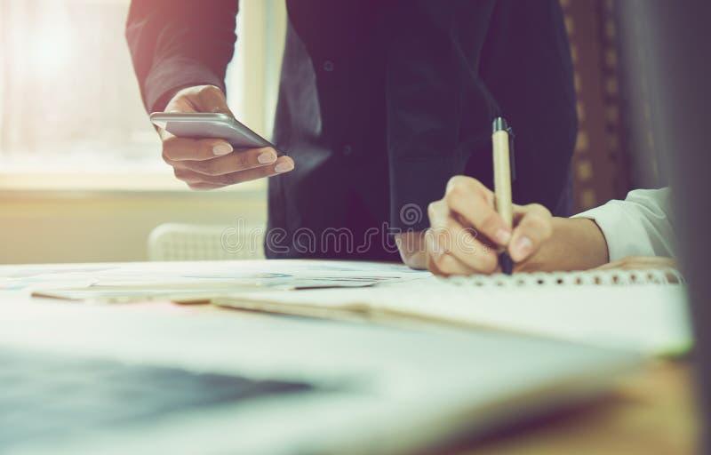 Mężczyzna i kobiety pracuje na drewnianym biurku w biurze w ranku zaświecamy Pojęcie nowożytna praca z zaawansowaną technologią R obraz royalty free