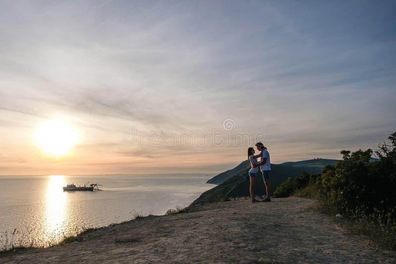 Mężczyzna i kobiety przytulenie na halnej drodze z seascape przy zmierzchem Boczny widok fotografia royalty free