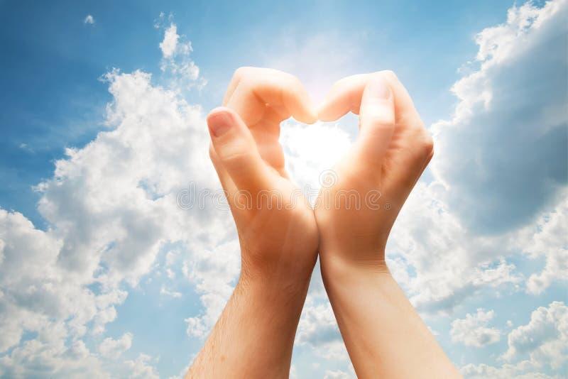 Mężczyzna i kobiety ręki robią sercu na błękitnym pogodnym niebie. Miłość obrazy royalty free