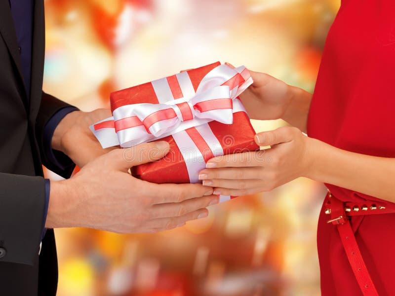 Mężczyzna i kobiety ręki z prezenta pudełkiem obraz royalty free