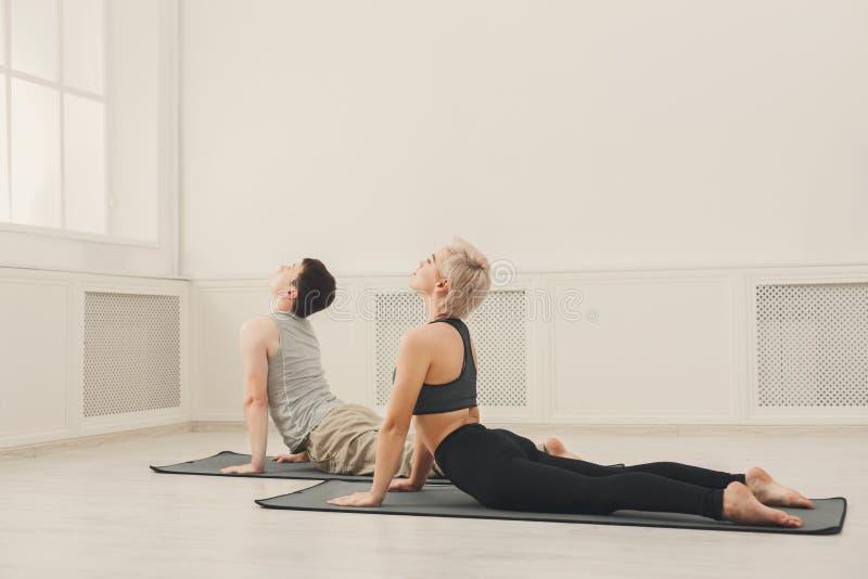Mężczyzna i kobiety stażowy joga w kobry pozie zdjęcie stock