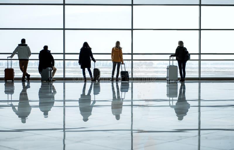 Mężczyzna i kobiety stoją przy śmiertelnie holem z bagażem zdjęcie royalty free